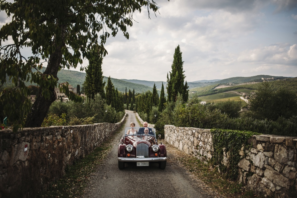 couple arriving with vintage car in a medieval castle in chianti tuscany