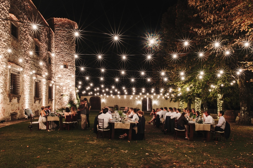 wedding dinner with bulblights in a medieval castle in chianti tuscany