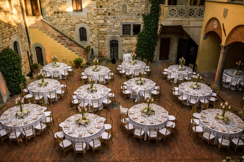 wedding dinner in a courtyard of a medieval castle in chianti tuscany