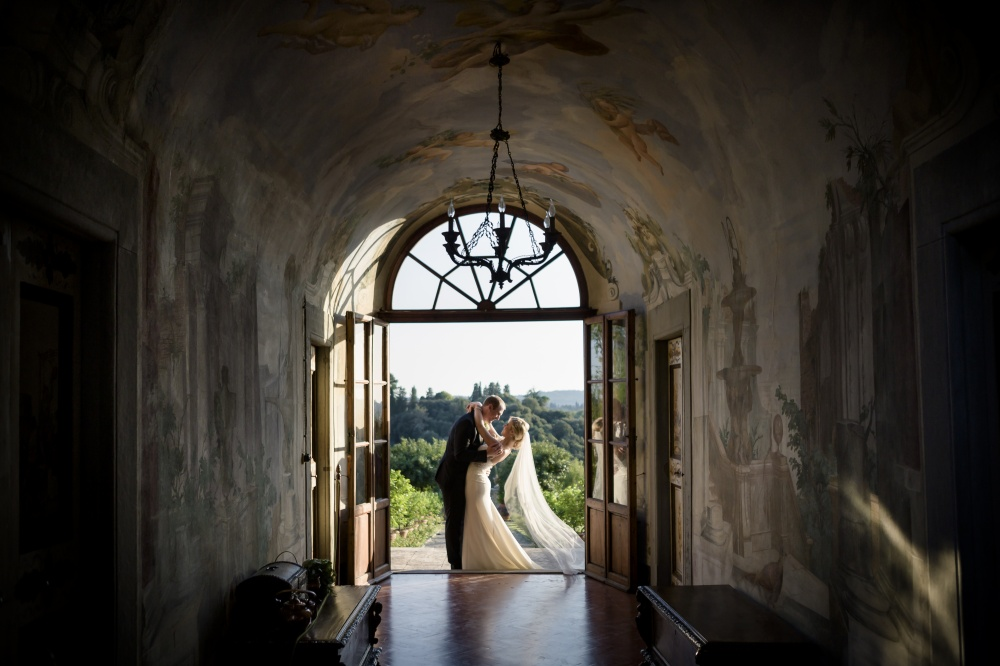 real couple with frescoes background in a one day rental villa in tuscany