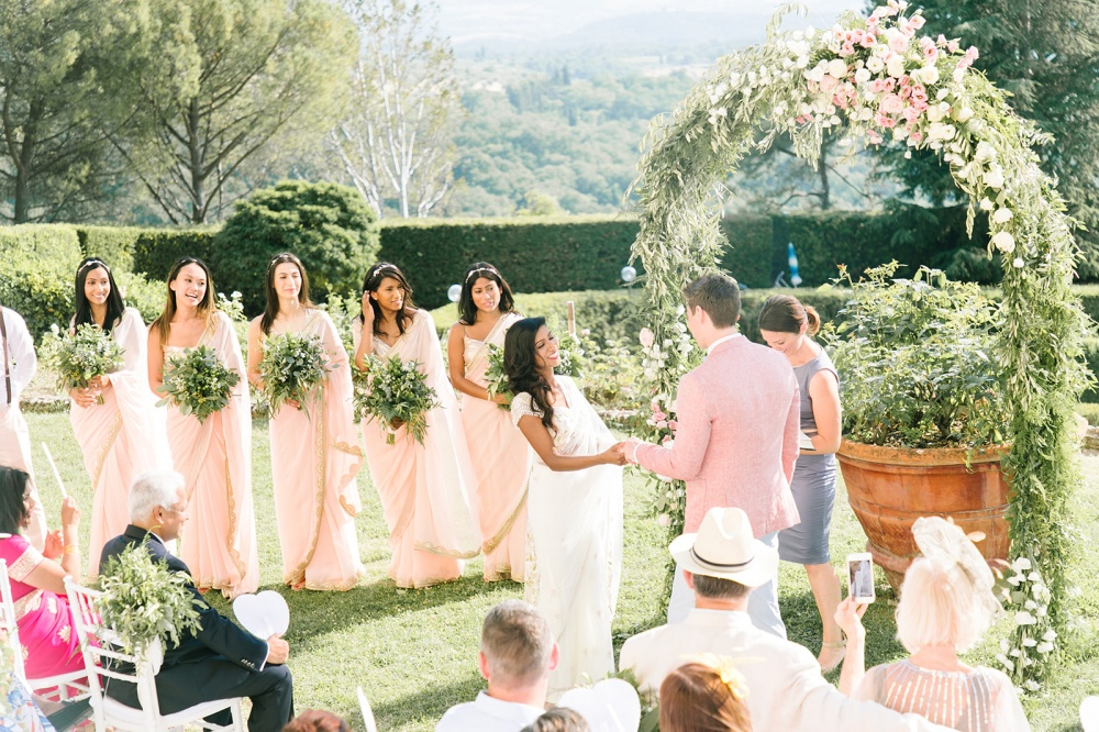 outdoor ceremony in tuscany arch with greenery and flowers