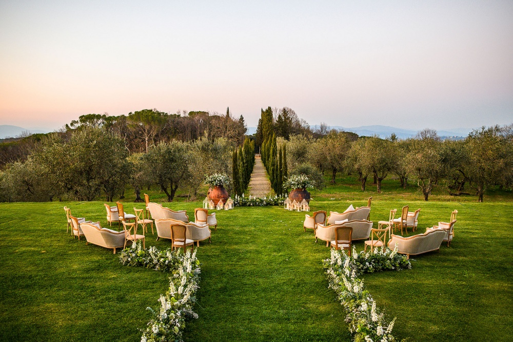 outdoor ceremony in tuscany with flowers and sofas