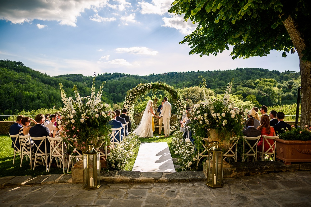 outdoor ceremony in tuscany with a rounded arch with flowers