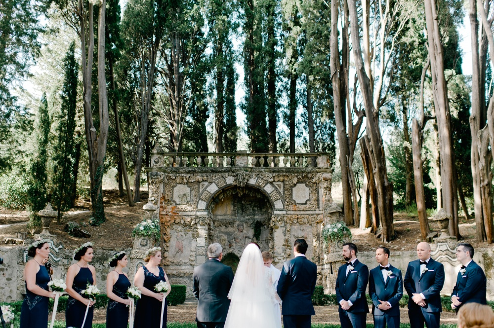 outdoor ceremony in tuscany grotto setting with wooden chairs