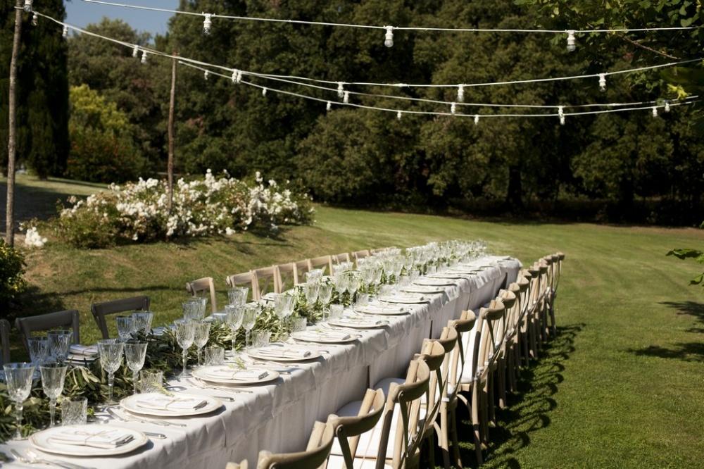 rectangular wedding dinner table with- vintage lights in a romatic weddin villa in siena