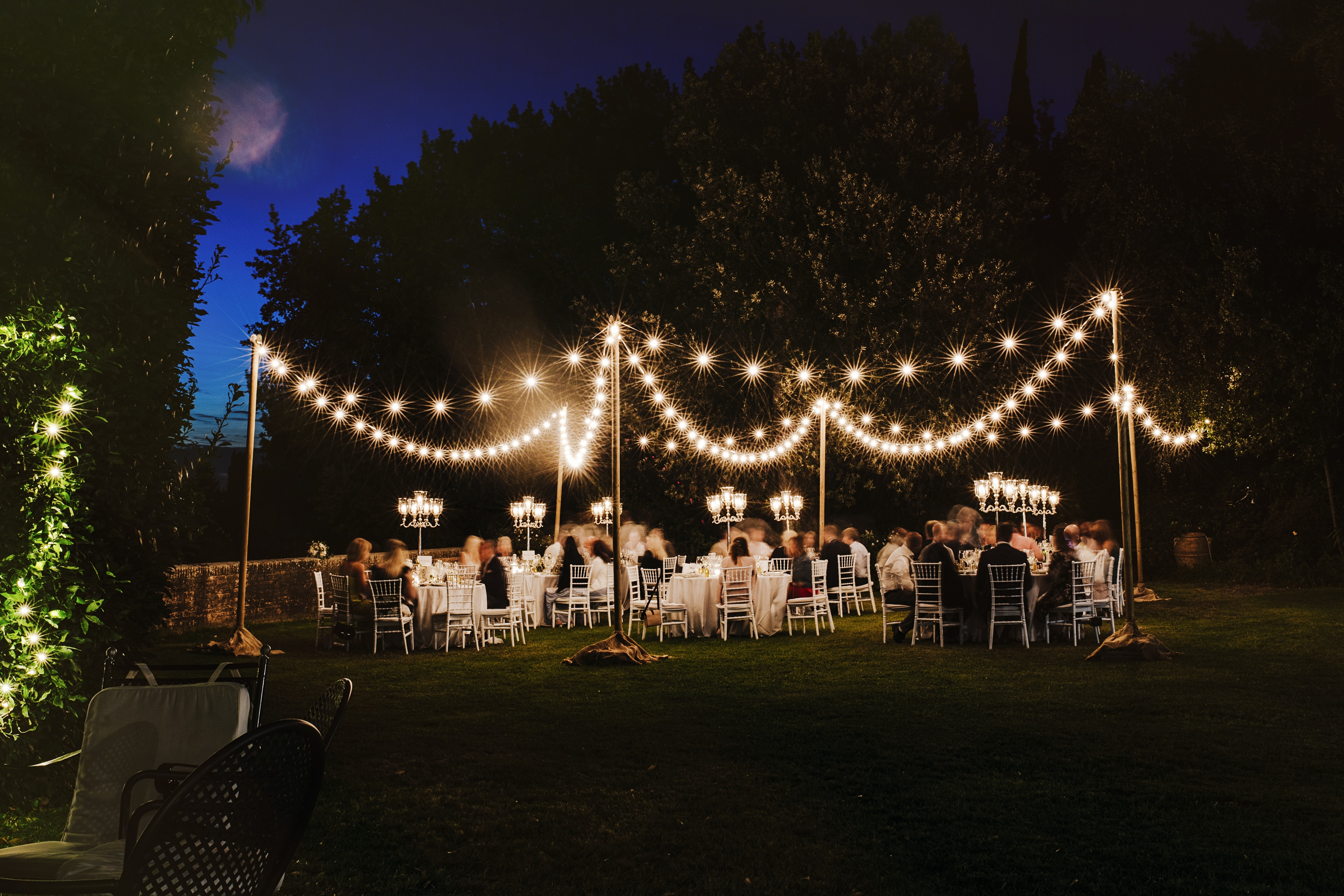 wedding dinner in the greenery of an ancient villa in Tuscany with a light show