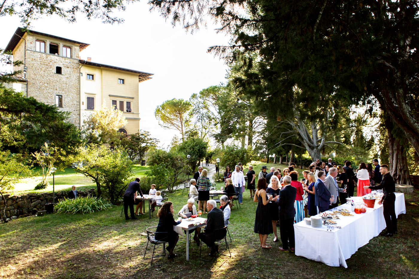wedding guests entertain themselves with an aperitif in the garden of the ancient villa in Tuscany