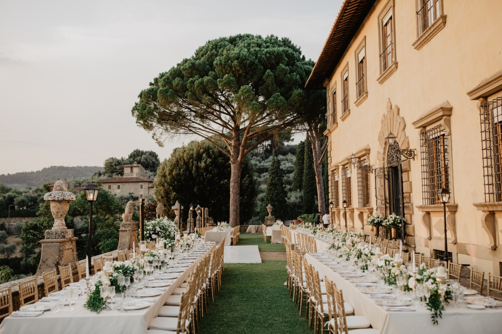 tuscan wedding villa with a dinner setting on its terrace next to the facade
