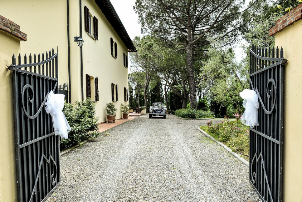 vintage car entering in the gate of a villa for weddings on the tuscan hills