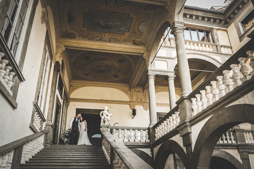real couple on stairs in a palace for wedding in lucca